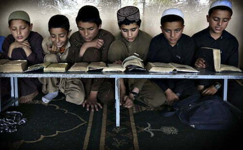 Boys read the Koran in a madrasa, or religious school, during th