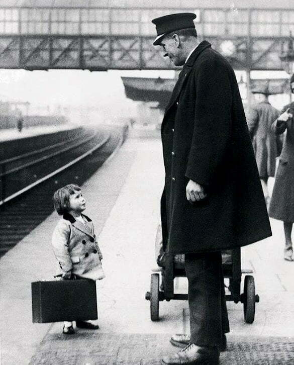 A young passenger asks a station attendant for directions. Bristol Railway Station, England, 1936 Photo George W. Hales
