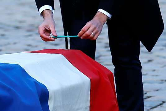 French President Emmanuel Macron places a pencil on the flag-draped coffin of Jean d'Ormesson, French author and member of the Academie Francaise, during a ceremony at the Hotel des Invalides in Paris, France, December 8, 2017. REUTERS/Francois Mori/Pool