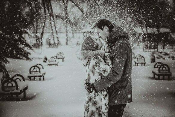Young couple kissing on snow. Black and white.